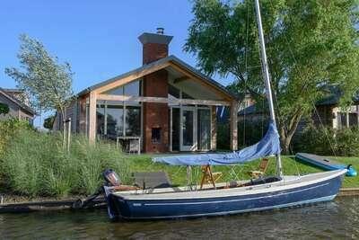 Bungalow moderne avec cheminée extérieure au bord de l'eau