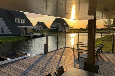 Villa au toit de chaume avec salon sur l'eau